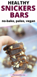 Pinterest image with text: two fingers close up holding a no-bake homemade snickers bar with caramel and peaunts