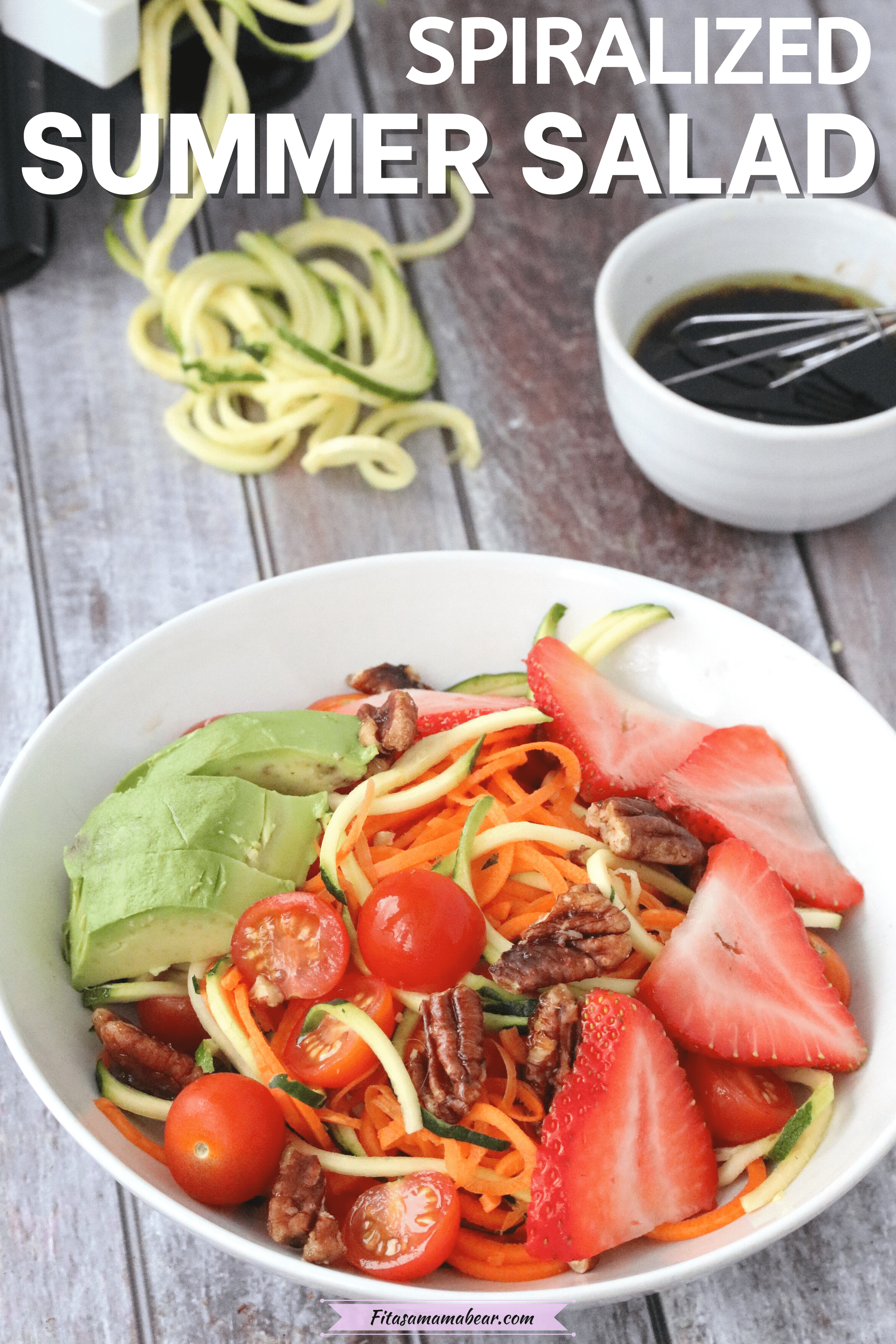 Pinterest image with text: Spiralized zucchini salad topped with strawberries, avocado and pecans with dressing and zucchini noodles behind it