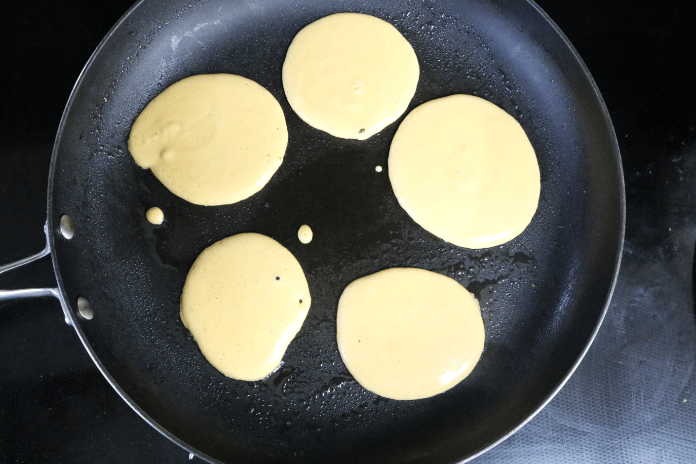 Five protein pancakes in a black pan