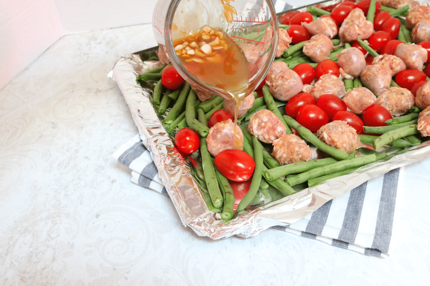 Glass measuring cup with honey garlic sauce being poured on a tinfoil lined pan with sausages, tomatoes and green beans