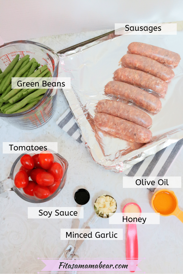Raw sausages on a baking tray with tomaotoes, green beans and spices in measuring spoons around it