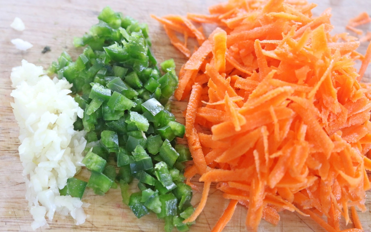 Carrots, green onion and onion all chopped on a wood cutting board