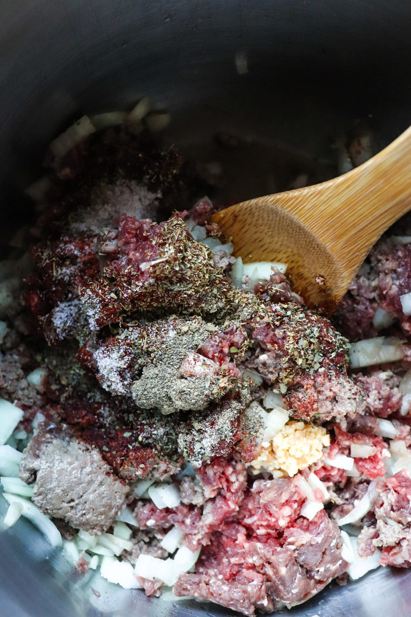 Ground venison, onion, and zucchini in a large pot being stirred by a wooden spoon
