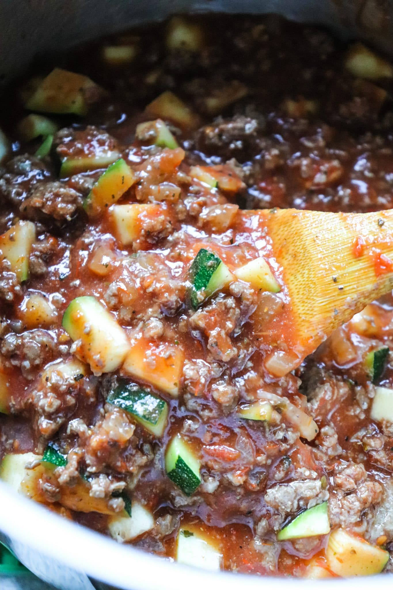 Ground venison, tomato sauce, onion, and zucchini in a large pot being stirred by a wooden spoon